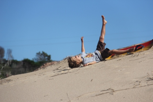 A young boy sand boarding in Punta del Diablo